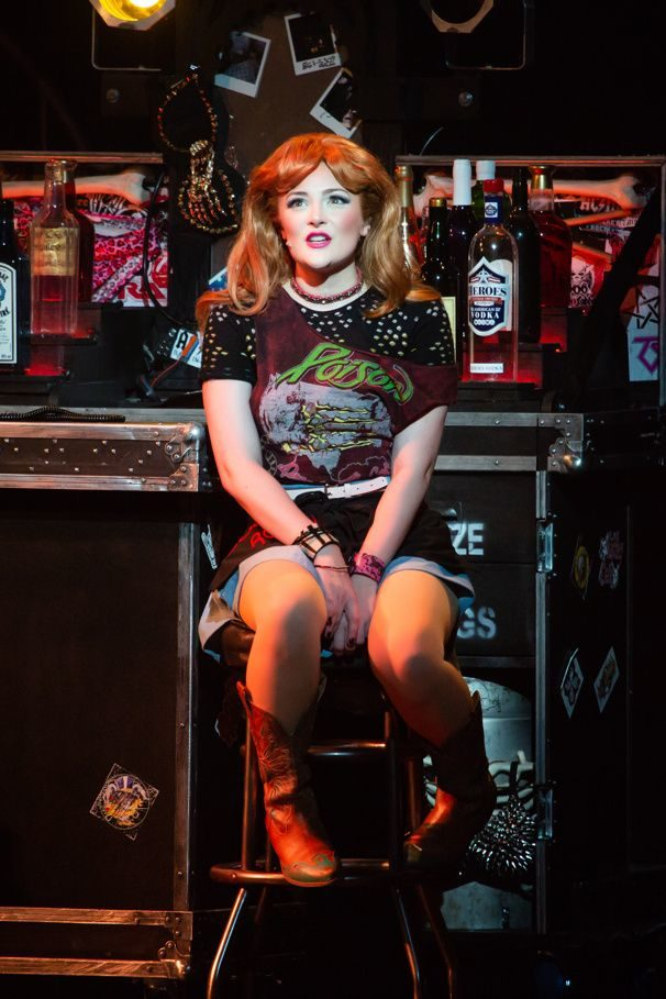 Red-haired woman sits on a bar stool, dressed in 80s fashion.