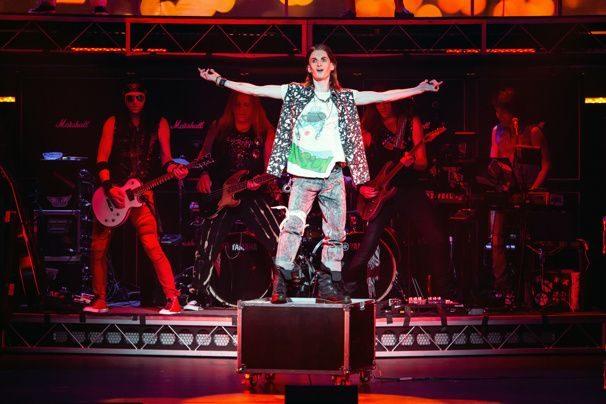 Rocker stands on some sound equipment.