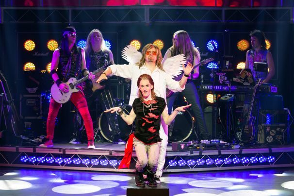 A rocker stands in front of a man dressed in white with fake angel wings to perform a choreographed dance.