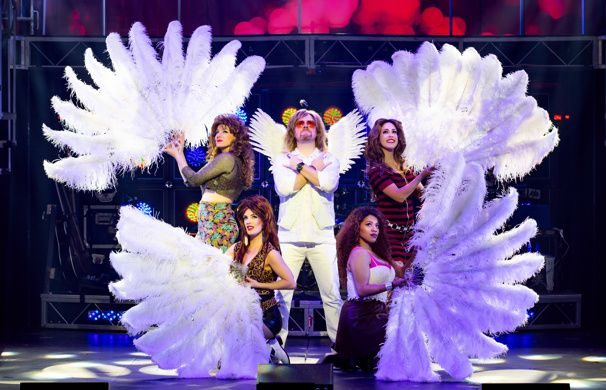 Man dressed in all white is surrounded by women holding feather fans burlesque style.