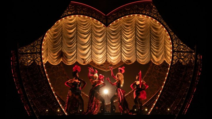 A production photo from Moulin Rouge! of four can-can dancers posing while backlit
