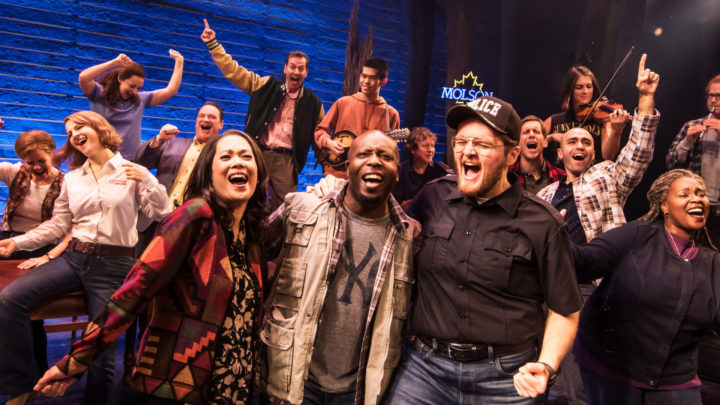 The company of the national tour of Come From Away join arms and sing together as they blow off steam at the bar